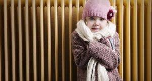 Rugged up child in front of heater